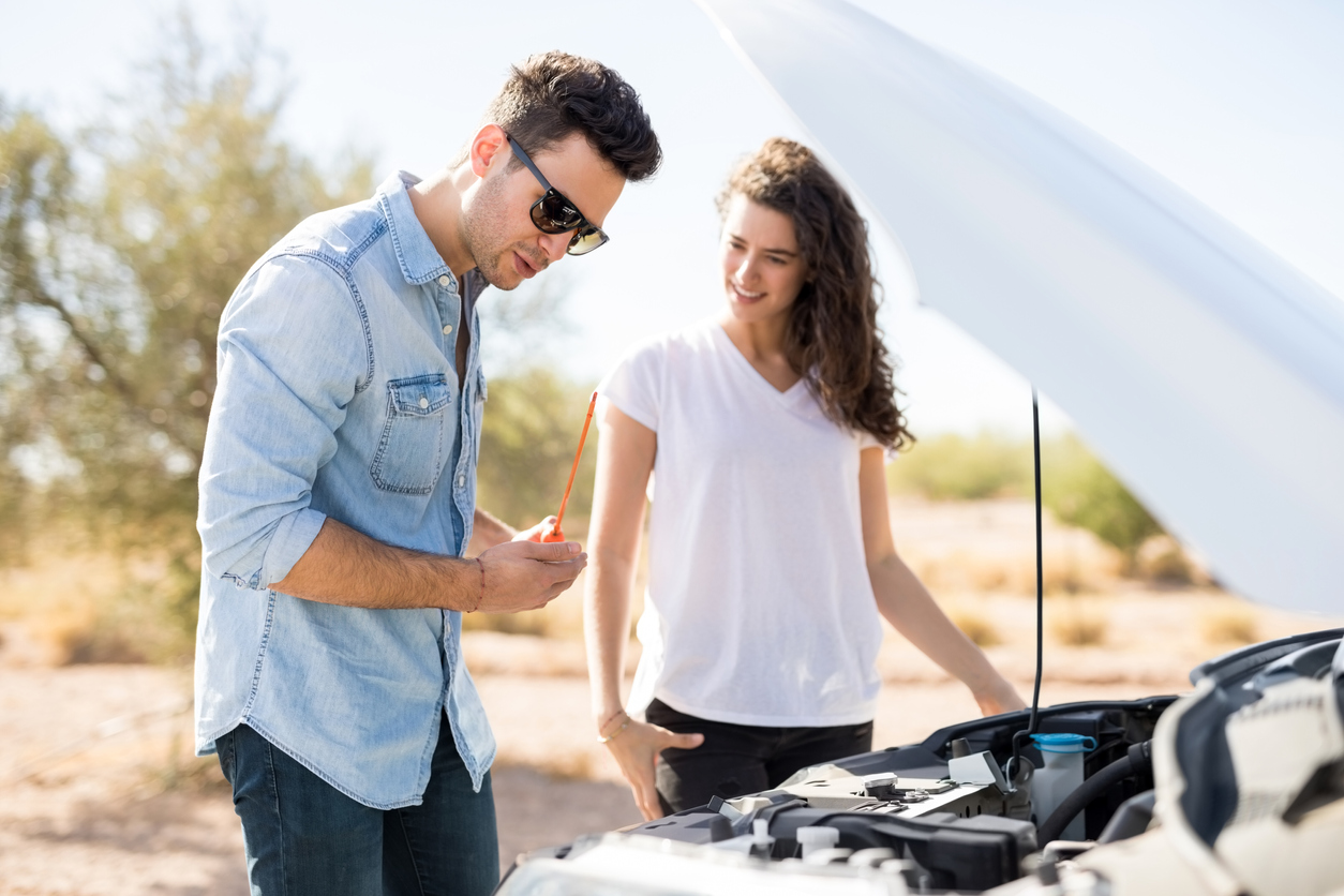 Man and women completing checks inside bonnet of car